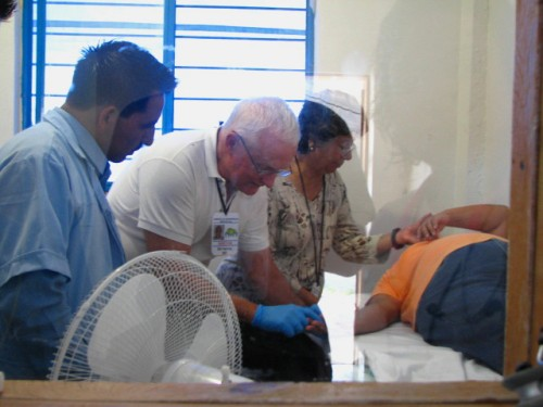 A Mexican EMT, Dr Bill Herring and an RN examine a patient